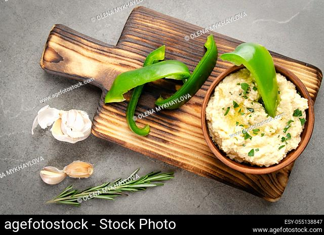 Flat lay view at vegetable Hummus dip dish topped with chickpeas and olive oil served with green sweet bell pepper slices