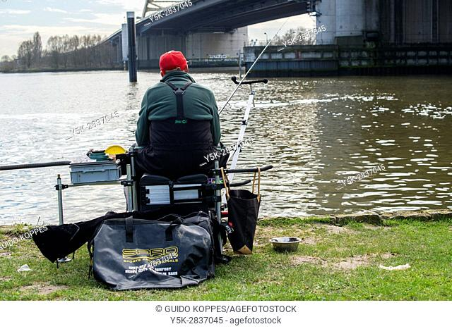 Rotterdam, Netherlands. Senior adult and retired male fishing for relaxation at the banks of Nieuwe Maas River, just under Van Brienenoordbrug at highway A16