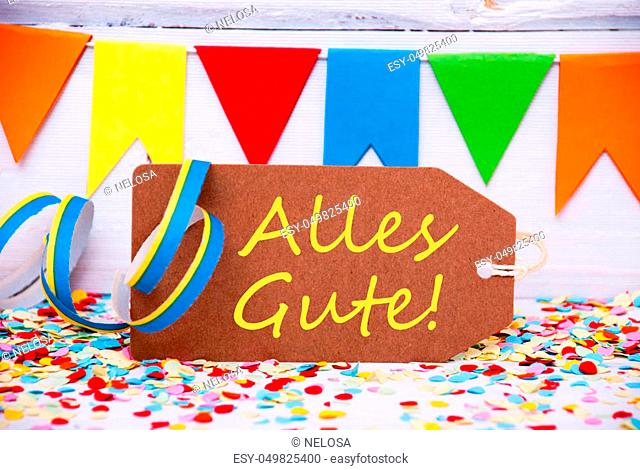 Brown Label With German Text Alles Gute Means Best Wishes. Party Decoration Like Streamer And Confetti. White Wooden Background