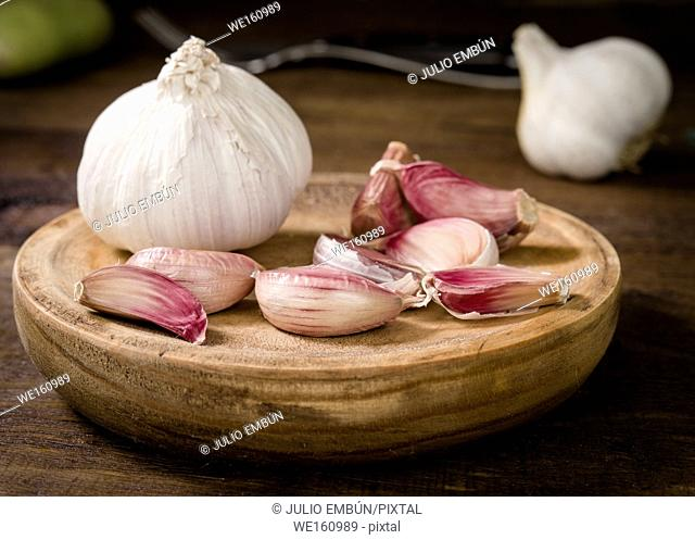 whole garlic cloves and heads in rustic wood