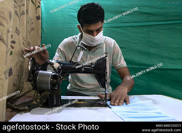 Central Reserve Police Force (CRPF) personnel use sewing machines while manufacturing face mask at the CRPF Northern Sector staff camp in New Delhi, India