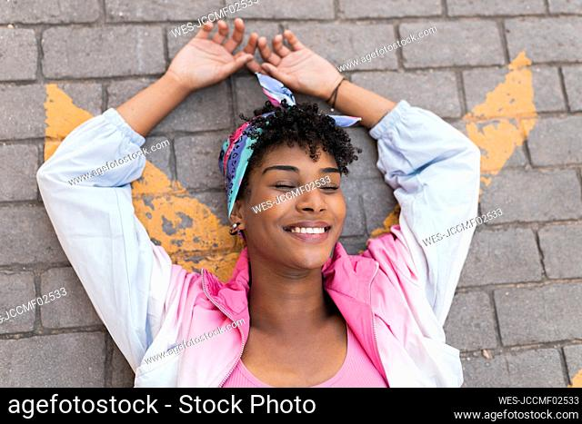 Carefree young woman with arms raised lying on road outdoors