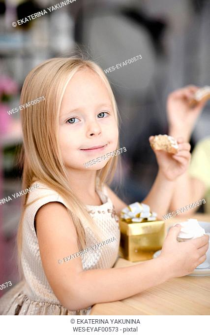 Portrait of smiling little girl with gift box eating cookies