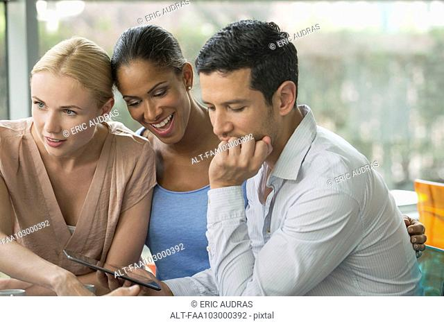 Man showing digital tablet to friends