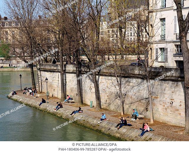 06 April 2018, France, Paris: Sunbathing in the Ile de Saint-Louis. Photo: Christian Böhmer/dpa. - Paris/Ile-de-France/France