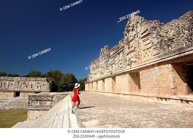 Tourist walking around the Quadrangle Of The Nuns in Uxmal ruins, Prehispanic Mayan city of Uxmal Archaeological Site, Yucatan Province, Mexico, Central America