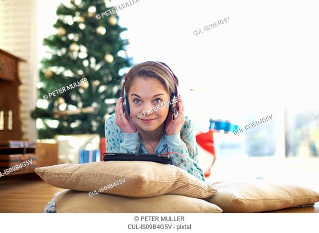 Girl lying on living room floor listening to headphones at Christmas