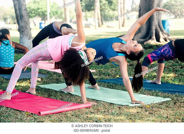 Schoolgirls practicing yoga pose on school playing field
