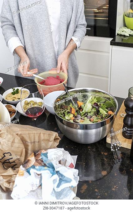 Woman preparing beetroot hummus and selection of vegetarian platers-mixed salad,green olive,hummus classic