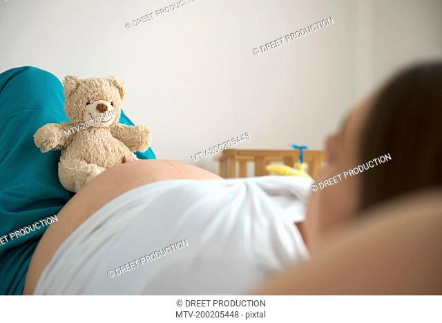 Pregnant woman bed lying holding toy teddy bear