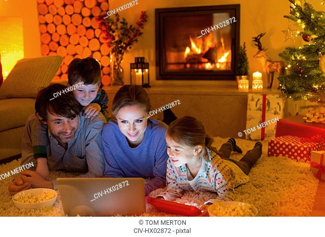 Family eating popcorn and watching video on laptop in ambient Christmas living room with fireplace