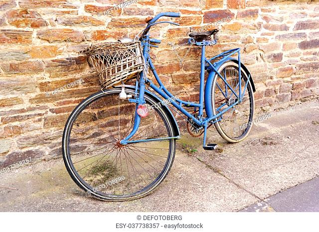 An old weathered blue bicycle with basket parked against a wall