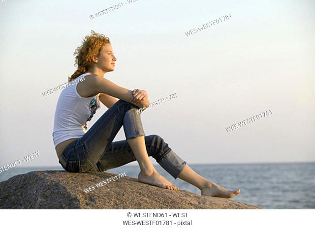 Young woman sitting on rock, side view