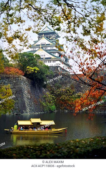 Osaka Castle, Osakajo and people taking a ride on Osaka-jo Gozabune Boat in Osaka Castle inner moat canal. Osaka Castle Park in a beautiful misty colorful...