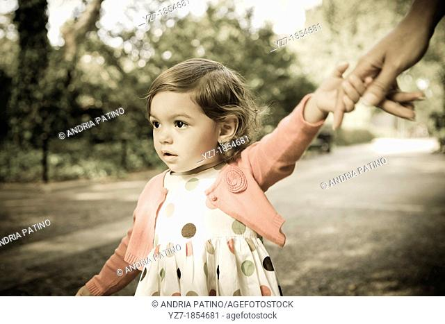 Toddler girl holding on to mother's hand