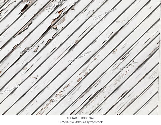 the diagonal line of the barn made of boards painted with white paint, part of the paint began to peel and slice from the tree