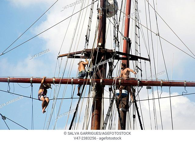 Three sailors working shirtless up the mast of the ship