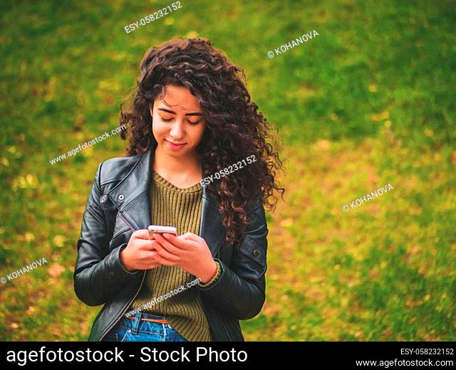 Portrait of relaxed young lady in autumn park reading a text message on mobile phone. Beautiful young african girl with dark curly hair using cell phone