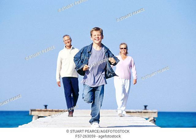 Father, mother and child walking in a wooden footbridge over the sea