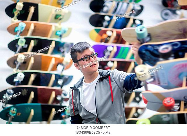 Young male skateboarder looking at skateboards in skateboard shop