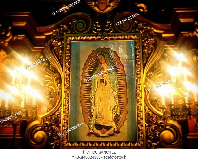 An image of Our Lady of Guadalupe surrounded by candles decorates the church of Santa Rosa de Lima in Condesa, Mexico City, Mexico