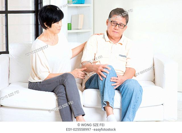 Asian old man knee pain, sitting on sofa with wife at home. Chinese family, senior retiree indoors living lifestyle