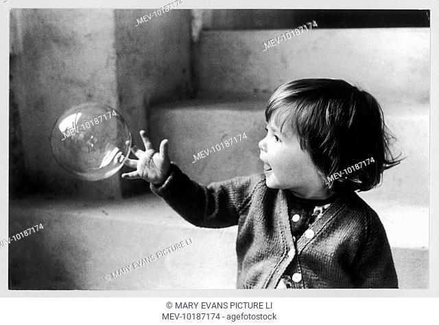 Katkin (daughter of Roger Mayne) playing with a bubble