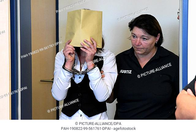 22 August 2019, Schleswig-Holstein, Itzehoe: With a concealed face, the defendant is led into the courtroom at the start of a murder trial