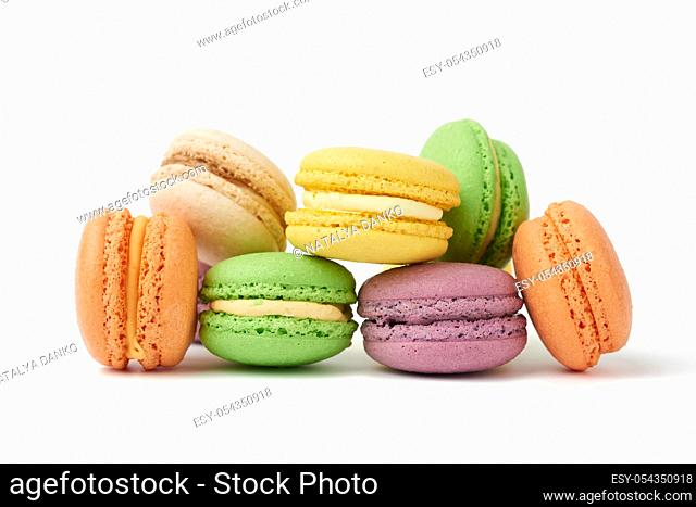 round baked multi-colored almond flour cakes macarons, dessert is laid out in a stack and isolated on a white background