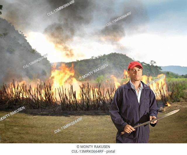 Worker In Front Of Burning Sugar Cane