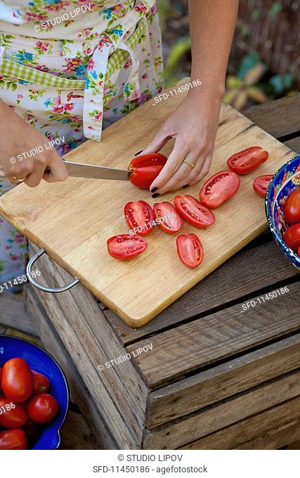A woman slicing tomatoes in a garden