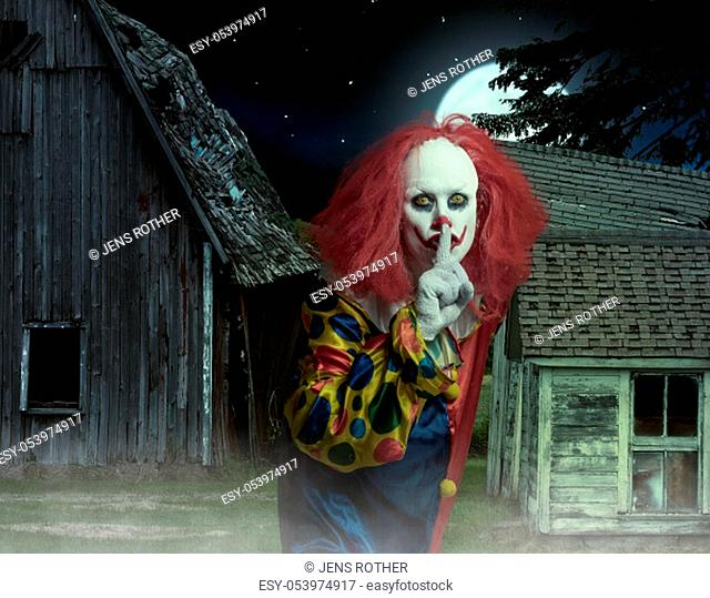 eerie clown with finger on mouth in front of a scary scene