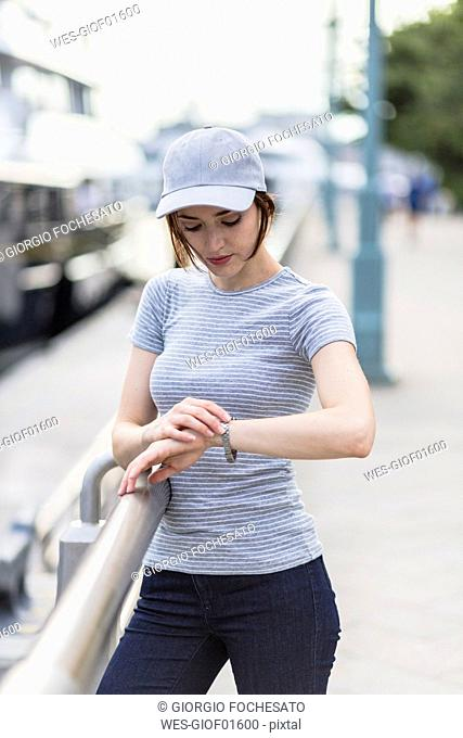 Woman with basecap checking the time
