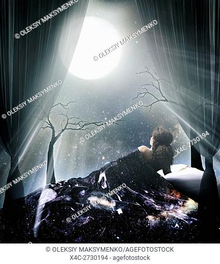 Lit by the moonlight woman lying in bed under the starry sky and the full moon artistic spiritual photo illustration concept