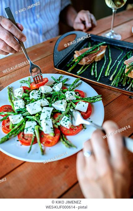 Hands of two persons eating salad of green asparagus, tomato slices and diced sheep cheese