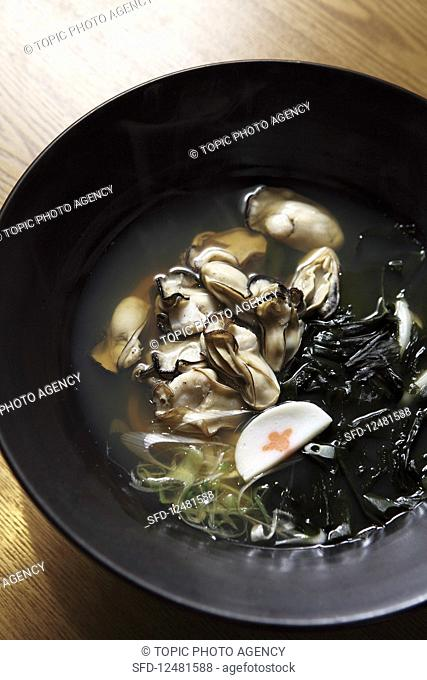 Oysters with black udon noodles in broth (Asia)