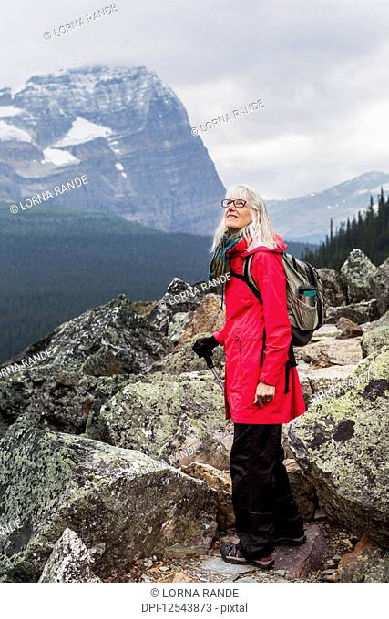 Female hiker looking up at the Rocky Mountains, Yoho National Park; British Columbia, Canada