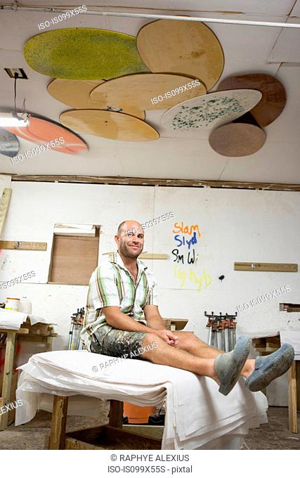 Portrait of man sitting in skimboard workshop