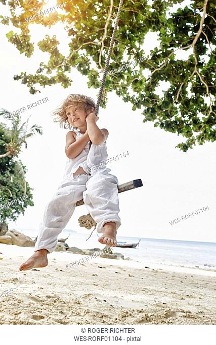 Thailand, Phi Phi Islands, Ko Phi Phi, smiling little girl on a rope swing on the beach