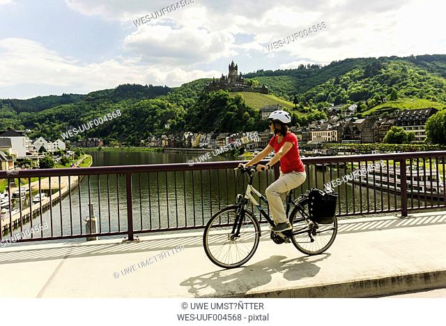 Germany, Cochem, cyclist passing bridge over Moselle