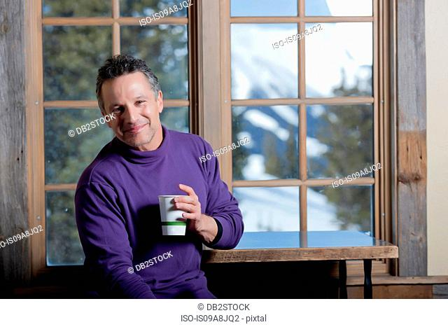 Mature man holding hot drink indoors, smiling