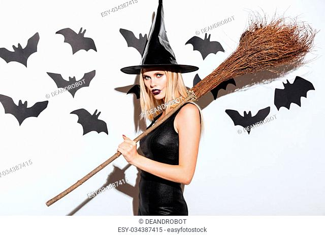 Portrait of beautiful young woman in black witch halloween costume with broom over white background