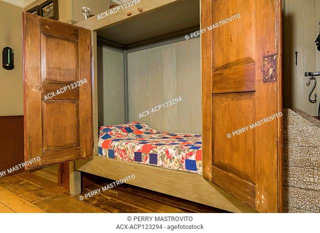 Single bed hidden in an old wooden armoire in the dining room inside an old circa 1805 Canadiana cottage style home, Quebec, Canada