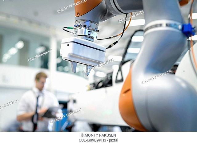Engineer and robot inspecting car in robotics research facility