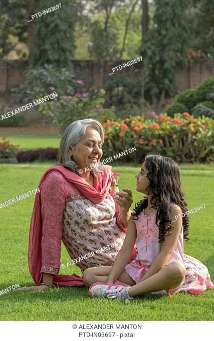 Grandmother looking at flower with granddaughter (4-5) in garden