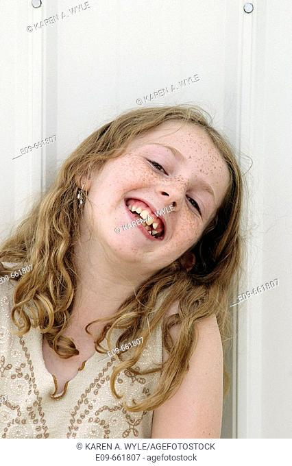 Preteen girl with wavy golden-brown hair and freckles, laughing with head toward one shoulder, leaning against white shed