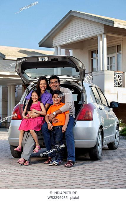 Family sitting at the back of a car