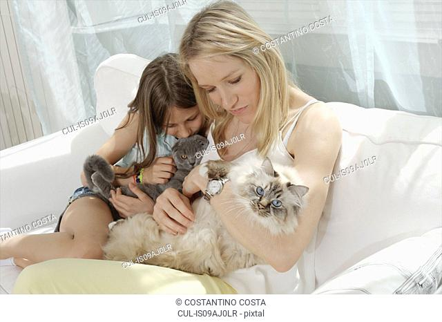 Mother and daughter on sofa hugging cats