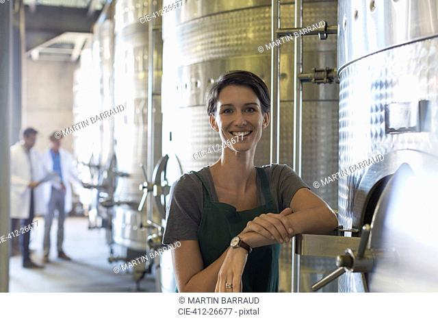 Portrait smiling vintner at stainless steel vat in winery cellar