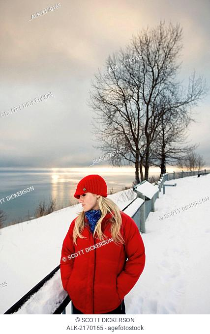 Young Woman Talks On Cell Phone At The Baycrest Pullout On The Sterling Highway Near Homer, Alaska During Winter